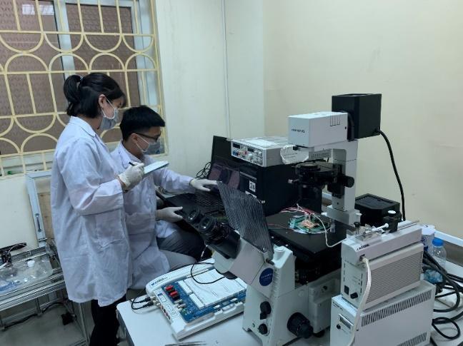 Nhóm nghiên cứu của Trường ĐH Công nghệ kiểm tra chip trong phòng thí nghiệm. Ảnh: IT